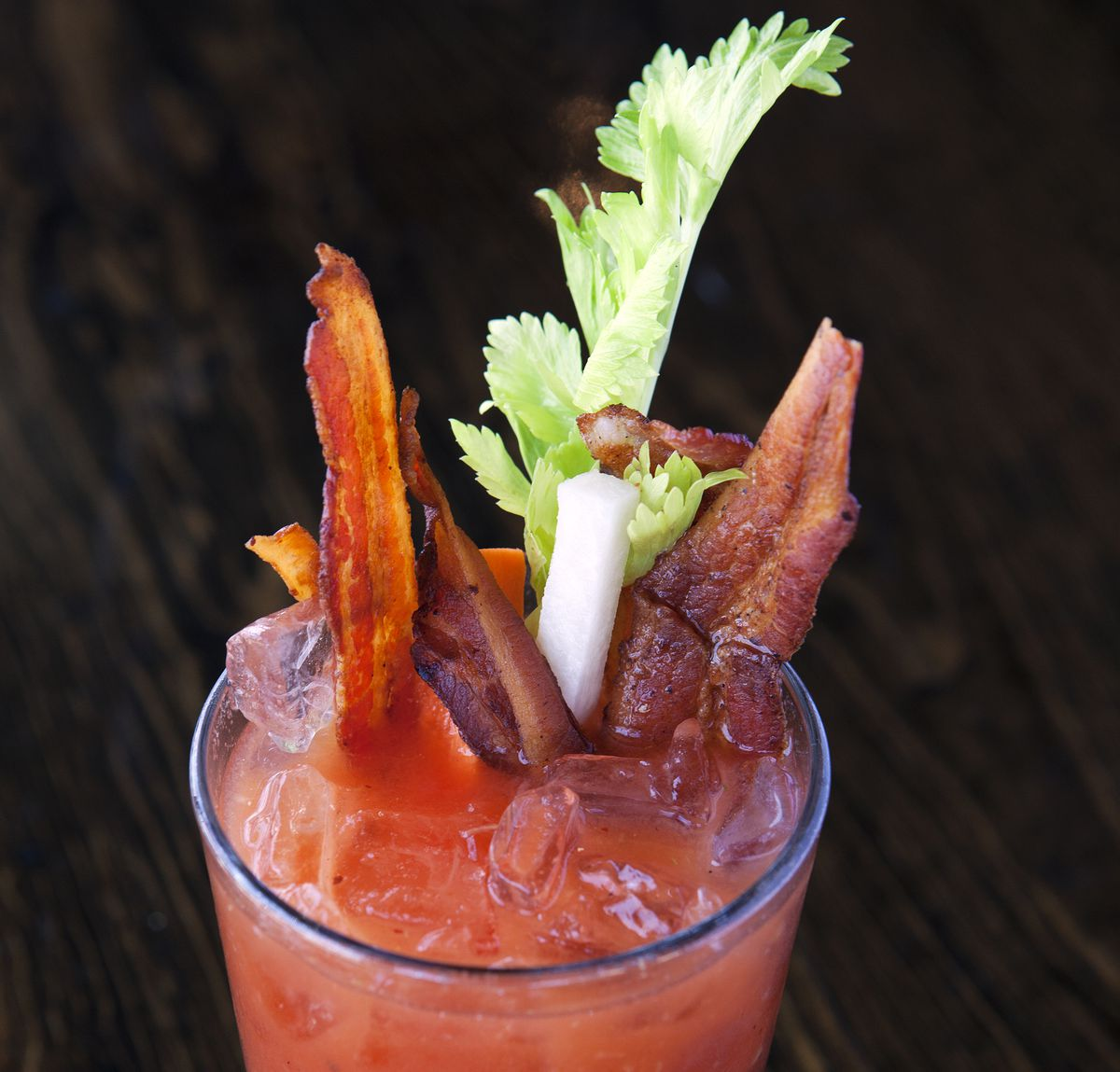 Close-up of a red liquid in a glass, with several strips of bacon also tucked in.