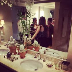 Partygoers hang out in the fancy marble bathroom.