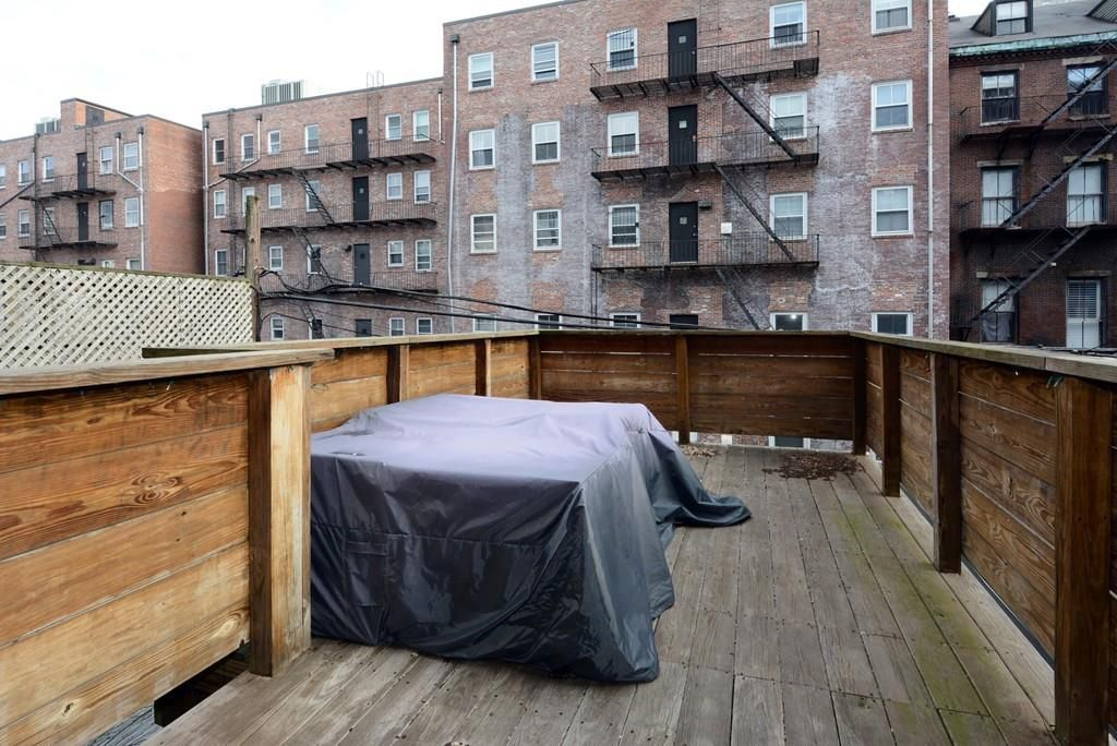 A long, narrow deck with a tarp covering what looks like a table, and the deck is otherwise empty.