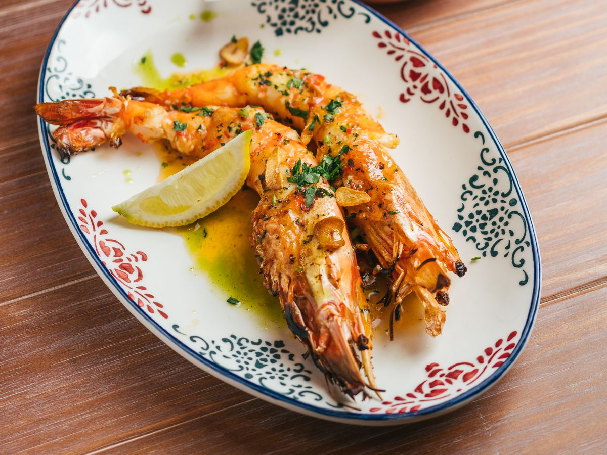 A decorative dish with two large prawns in oil with a slice of lemon beside a wax paper-lined copper pan full of french fries on a wooden tabletop