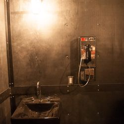 """The men's room, with walls made of roofing membrane and the """"crazy ass payphone."""""""