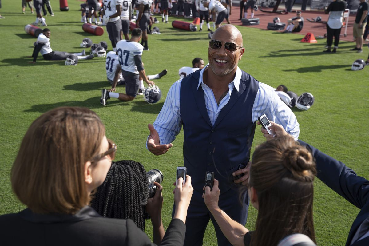the rock speaks to a handful of reporters on the side of a football field in ballers