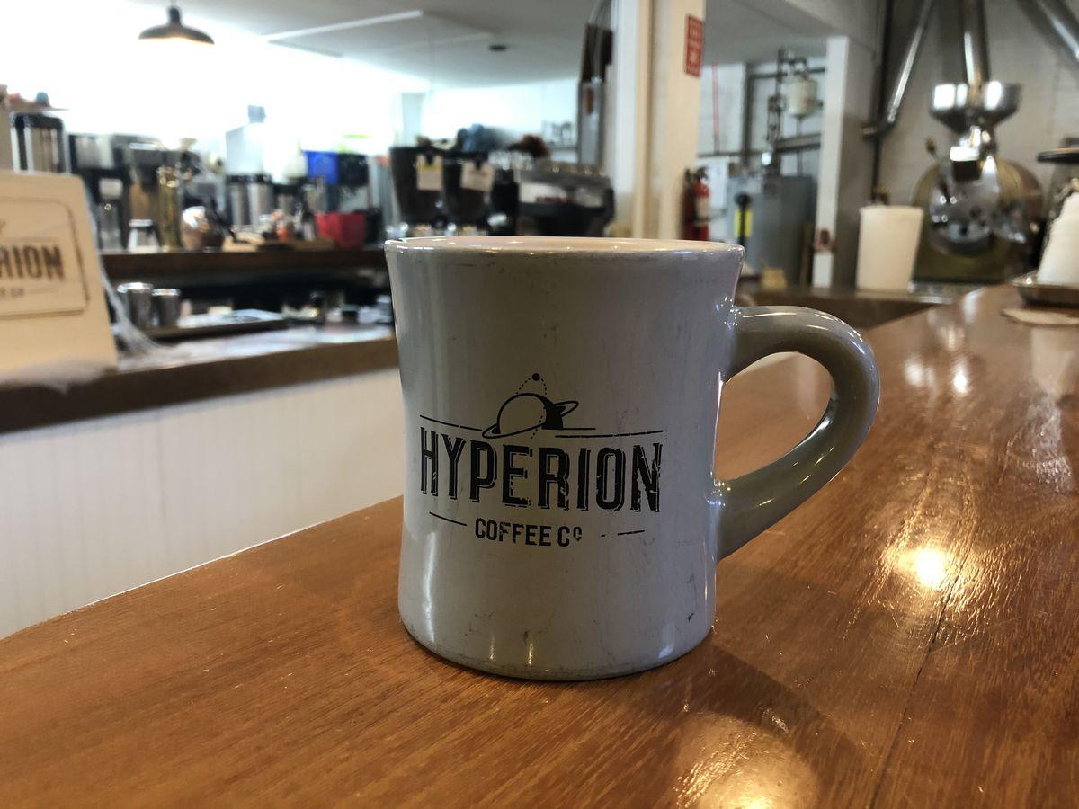 A white coffee mug with a Hyperion logo sits on a wood bar.