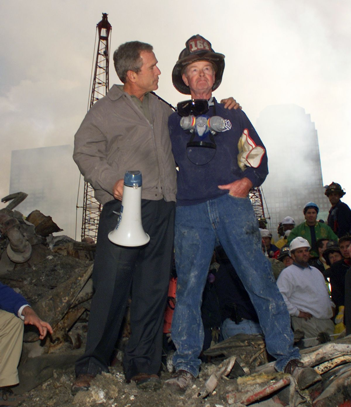 In this Sept. 14, 2001 file photo, President George W. Bush embraces firefighter Bob Beckwith while standing in front of the collapsed World Trade Center buildings in New York as rescue efforts continue.