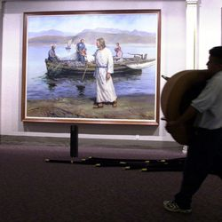 A worker carries a chair past restored murals in the North Visitors' Center as crews work to finish remodeling the two visitors centers on Temple Square Friday, Sept. 21, 2001.