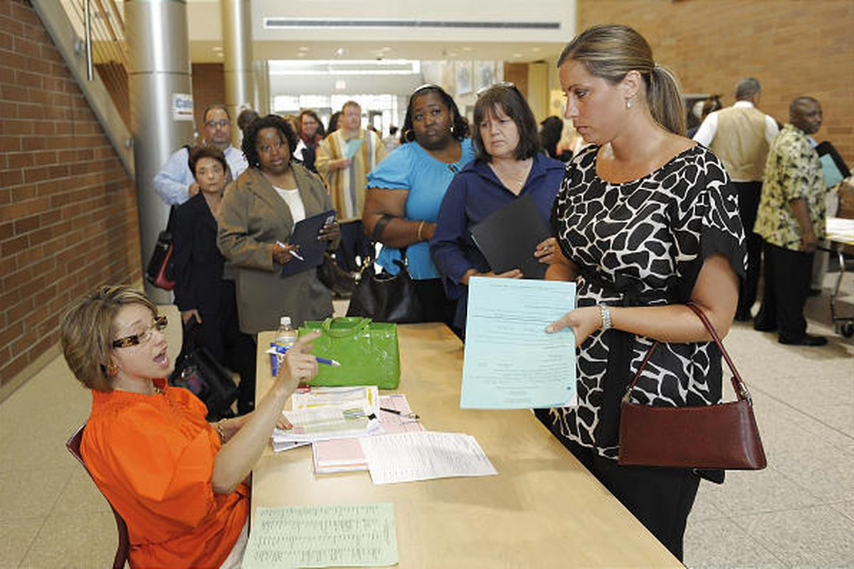 In this Aug. 10 photo, Lois Hussain, left, a special education administrator, gives instructions to Meghan Flowers, a special ed. teacher at Southwestern H.S., before she goes on her interviews in Detroit.