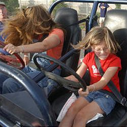 """UHP trooper Todd Johnson watches as Shannon Acor and daughter Payton, 8, test the Utah Highway Patrol's """"Seat Belt Convincer."""""""