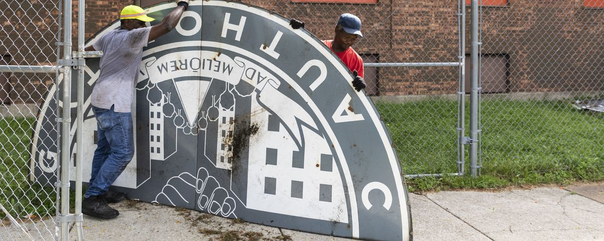 Thomas Taylor (grey shirt), 54, of North Lawndale, and 59-year-old Wayne Flax, of Austin, workers with McKay Landscaping, work to dismantle and take into storage an old Chicago Housing Authority sign outside the sole remaining building from the Jane Addam