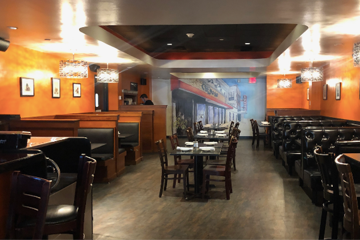 A dimly-lit dining room with high-top tables and orange walls at the Fat Cat in Quincy, MA.