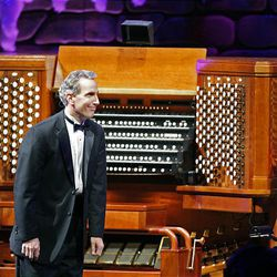 """Organist Richard Elliott acknowledges a standing ovation for his rendition of """"Good King Wencesla,"""" as the Mormon Tabernacle Choir, singer Natalie Cole and author David McCullough perform at the annual Christmas concert at the Conference Center in Salt Lake Friday."""