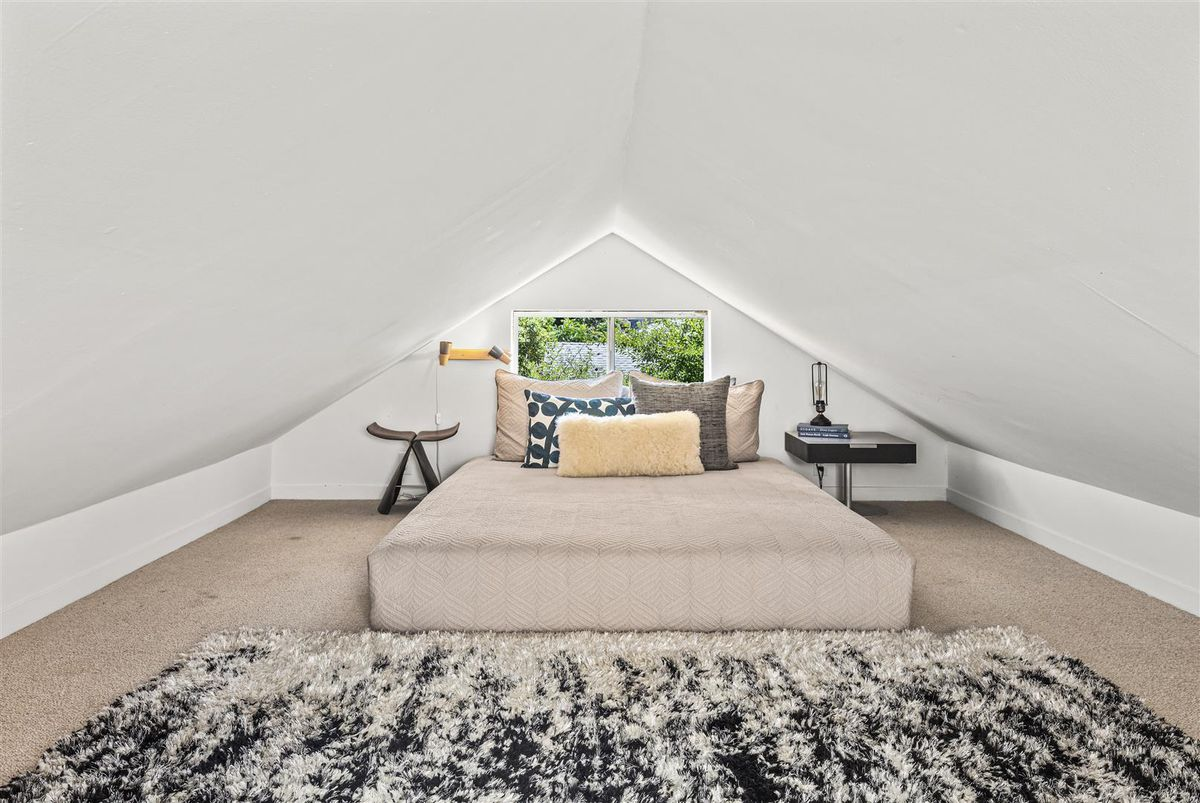 An attic space with white walls, peaked roof, and a bed. There's a window at the head of the bed that overlooks the yard.