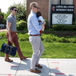 """Brooks Brunson, left, walks with his husband, Gregg Pitts, holding their son Thomas Brunson-Pitts, as the family arrives to attend church at Capitol Hill United Methodist Church in Washington, on May 8, 2016. Half of U.S. adults believe religious responses to LGBT issues alienate young people, who may be turned off by a """"judgmental"""" stance toward gays and lesbians."""