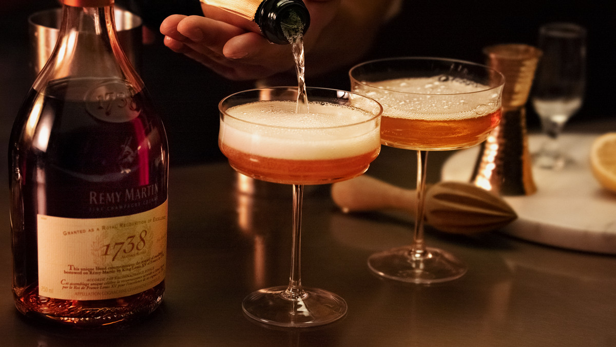 On a wooden table, there is a bottle of Rémy Martin 1738 Accord Royal, along with cocktail-making supplies like a metal jigger. Two pink-orange cocktails in coupe glasses sit front and center, with a hand pouring a bottle of Champagne to top off one of the drinks.