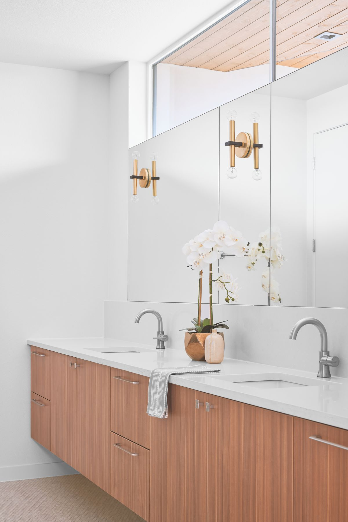 Photo of part of a bathroom with a long counter with two sinks and wood-fronted cabinets wit a long mirror in back and a long clerestory window above.