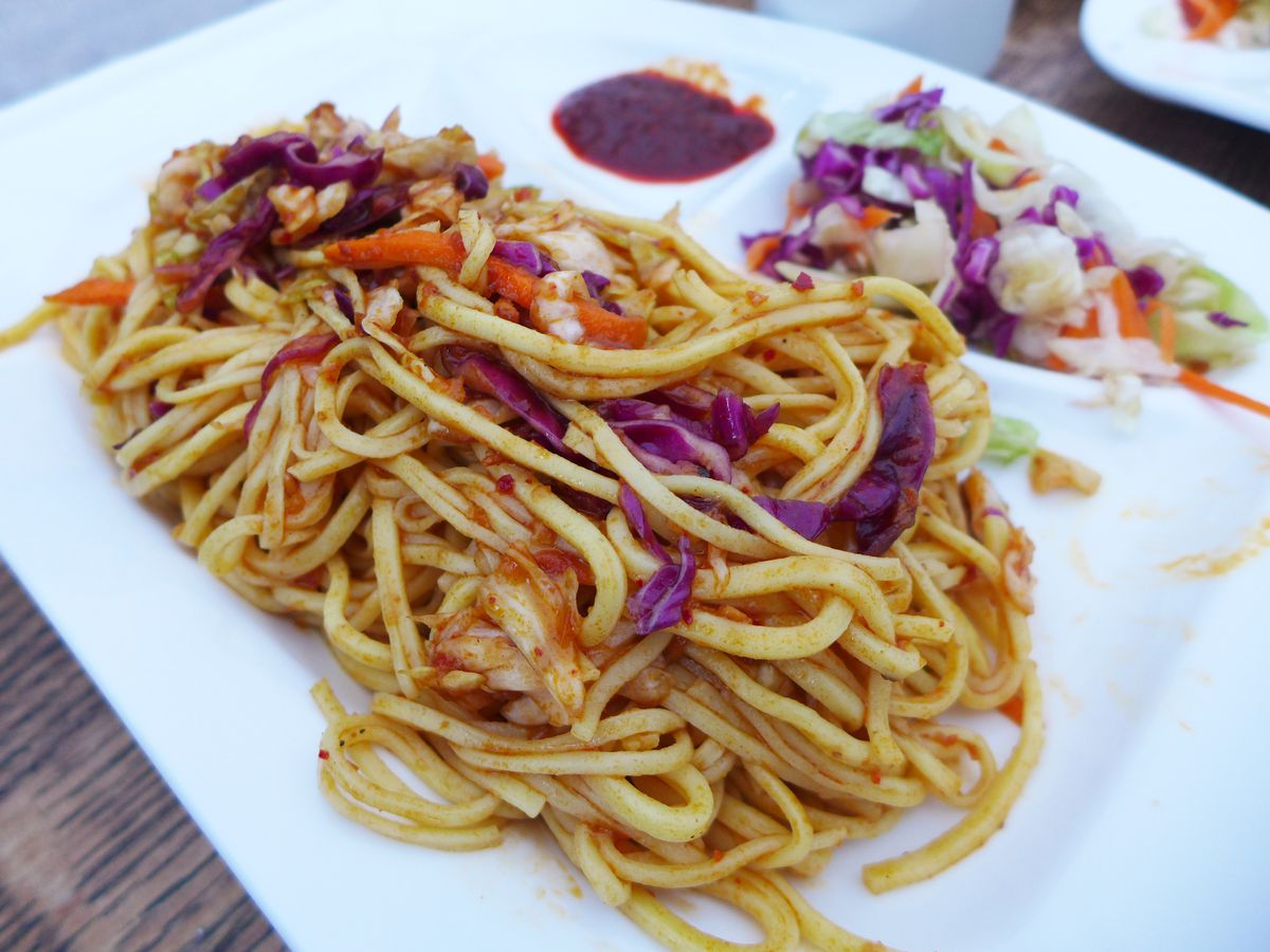A platter of linguine with sparse red sauce.