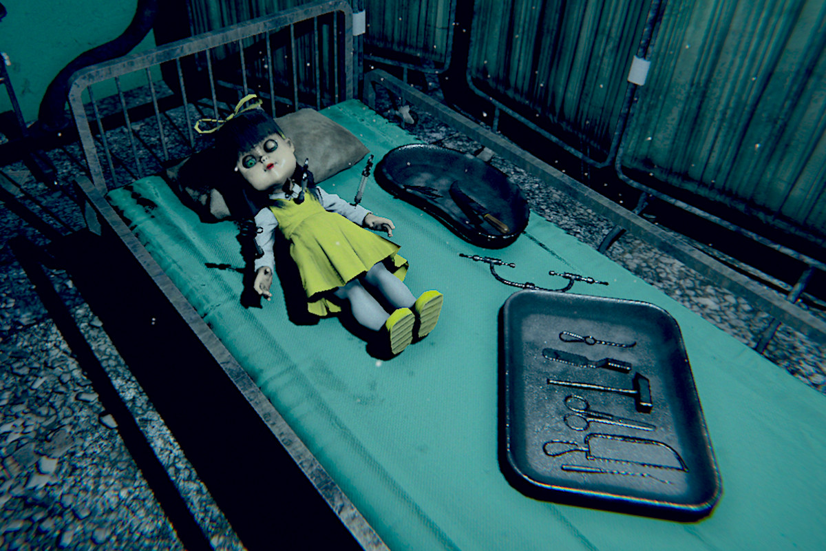 a doll lying on a bed alongside a tray of medical instruments in Devotion