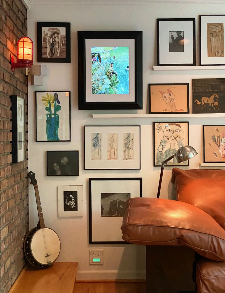 A digital photo frame with a black frame hangs on a wall with a bunch of other black-framed artworks.