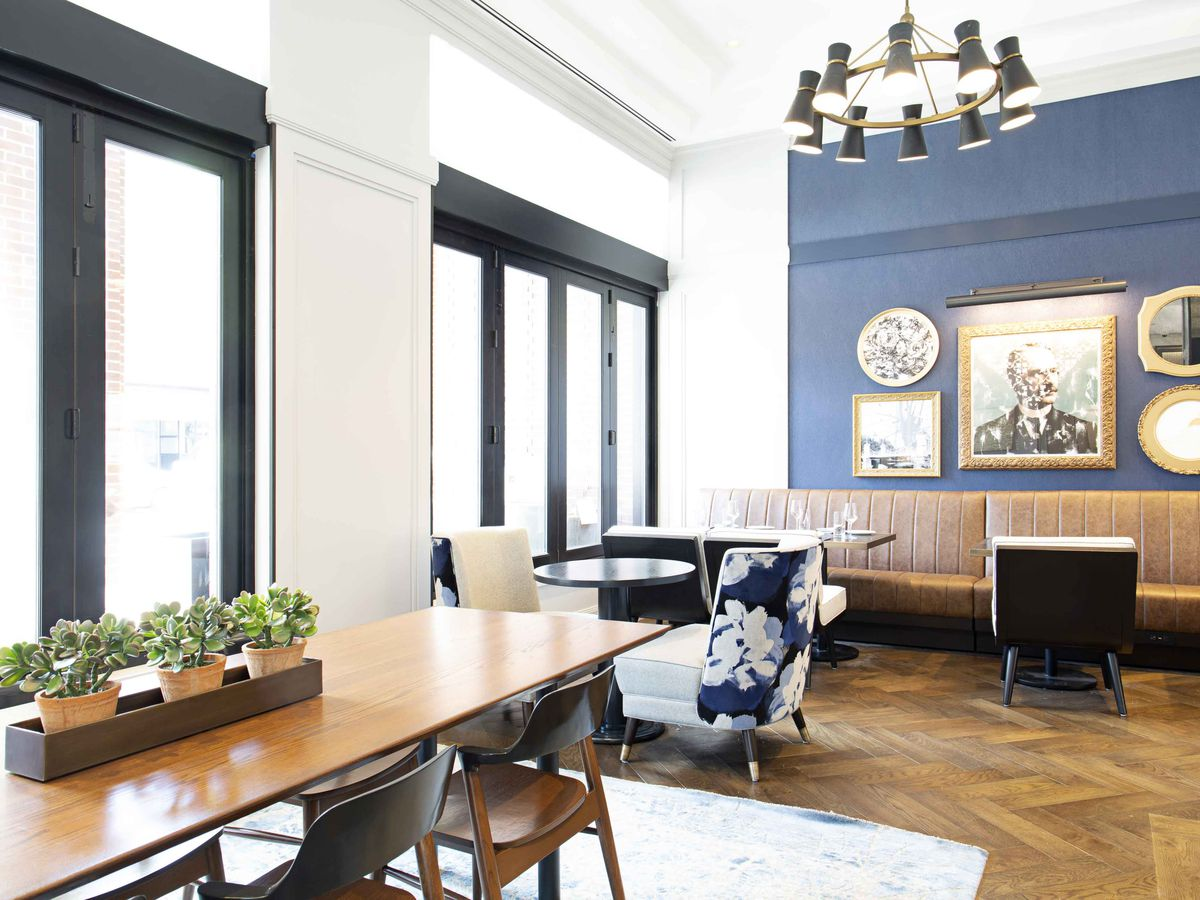 An interior photo of Peregrine in the lobby of the Whitney Hotel in Boston's Beacon Hill. Nearly floor-to-ceiling windows fill the wall along the street, and a blue wall covered with art is visible in the background.