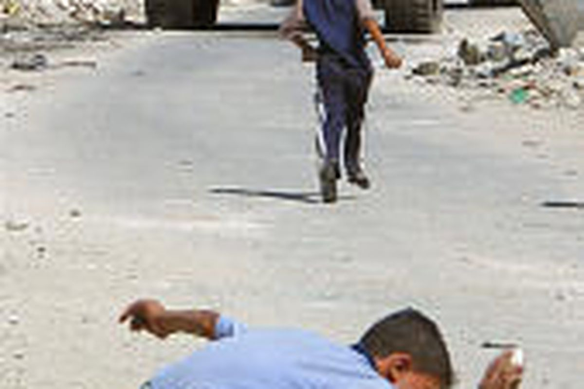 A Palestinian boy smashes a stone as another boy runs toward Israeli tanks  during small-scale clashes in the northern West Bank town of Jenin on Wednesday.