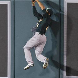 Oakland Athletics center fielder Coco Crisp goes to the wall to rob Los Angeles Angels' Kendrys Morales of a home run during the fifth inning of a baseball game in Anaheim, Calif., Monday, April 16, 2012.