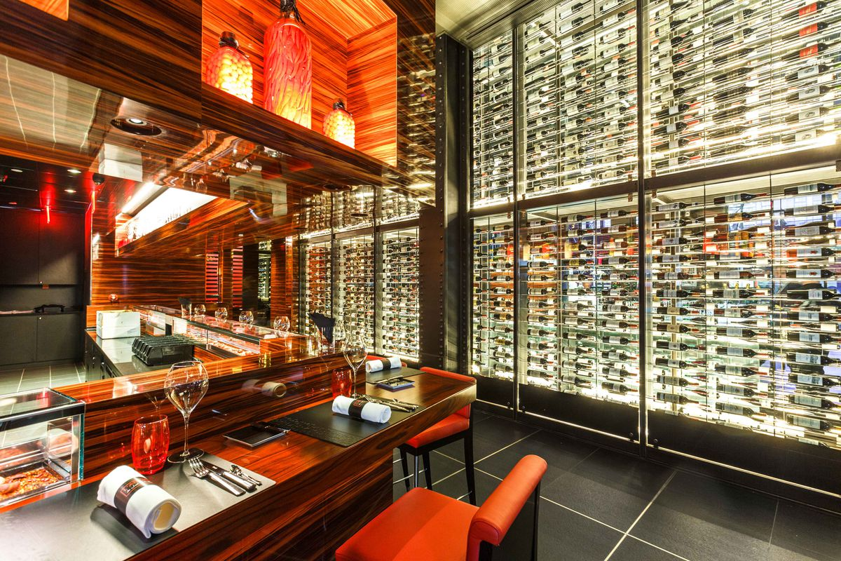 A red bar with a wall full of wine behind
