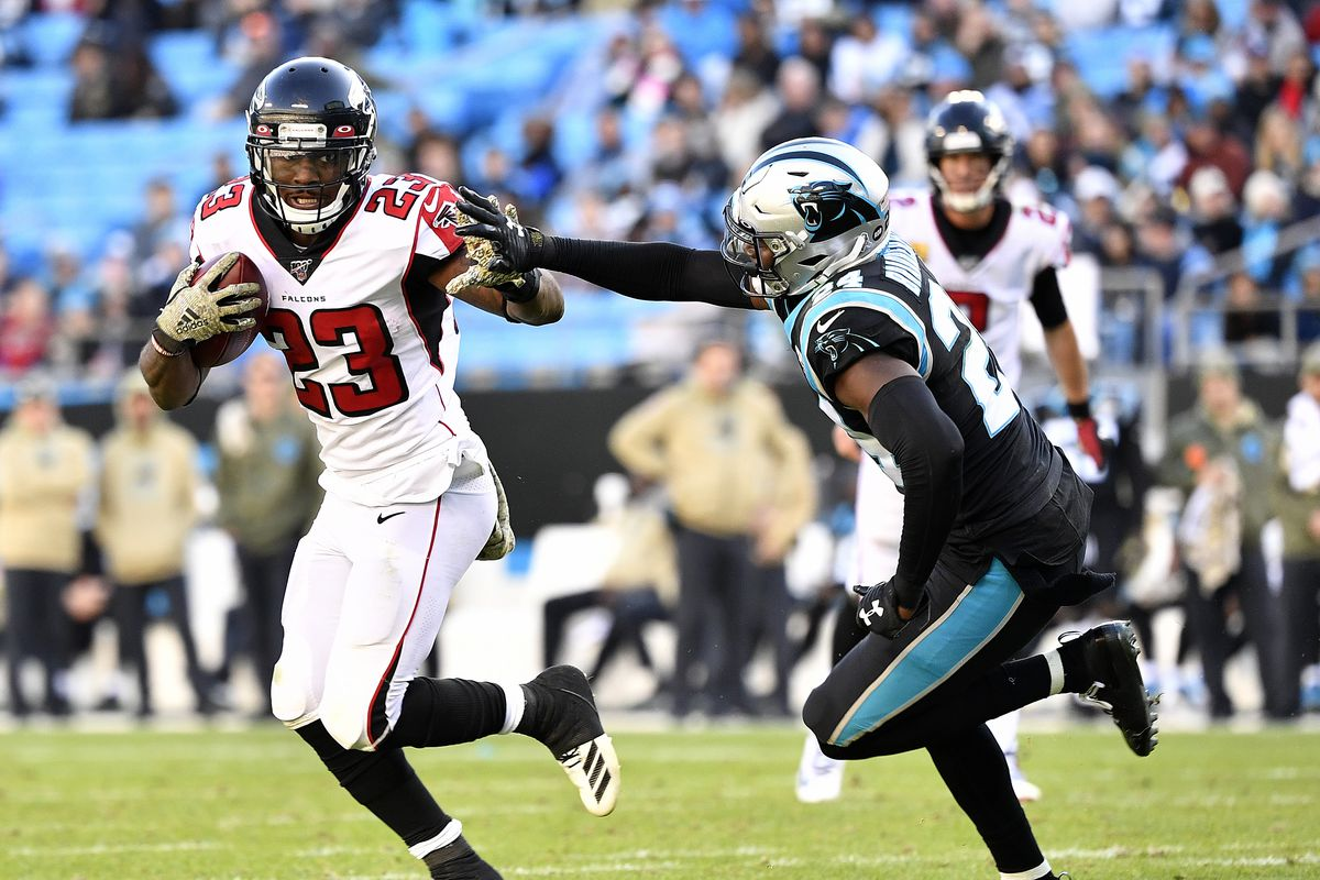 Brian Hill of the Atlanta Falcons runs against James Bradberry of the Carolina Panthersduring the third quarter of their game at Bank of America Stadium on November 17, 2019 in Charlotte, North Carolina.