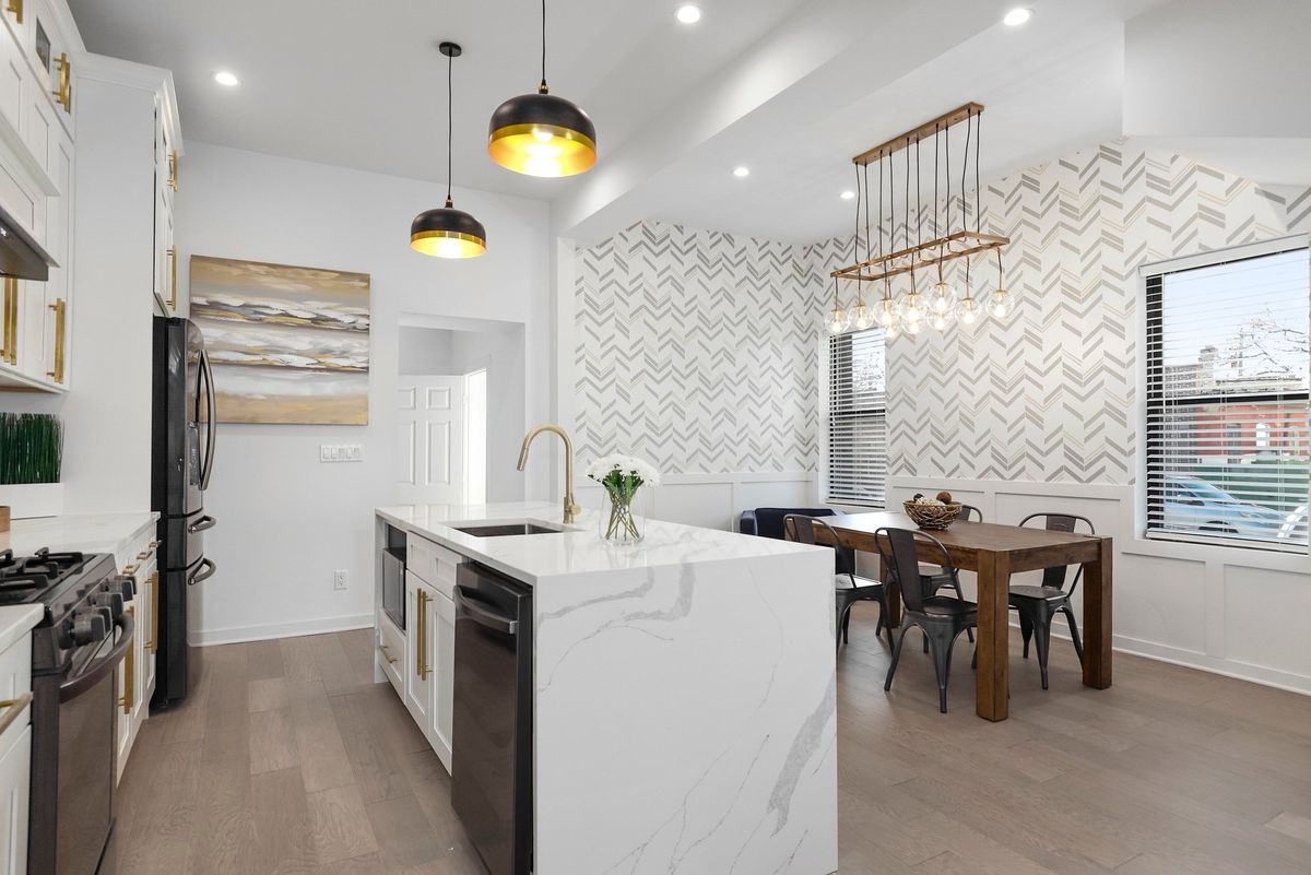 An open kitchen and dining area. There is a large island, gold light fixtures, and geometric wallpaper.