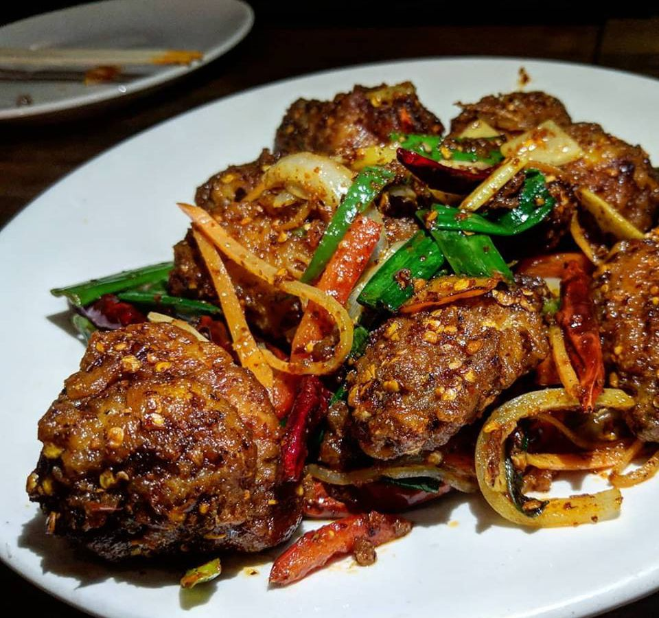 Meaty fried chicken wings sit on a white plate, topped with chile flakes and strips of onions, peppers, and scallions