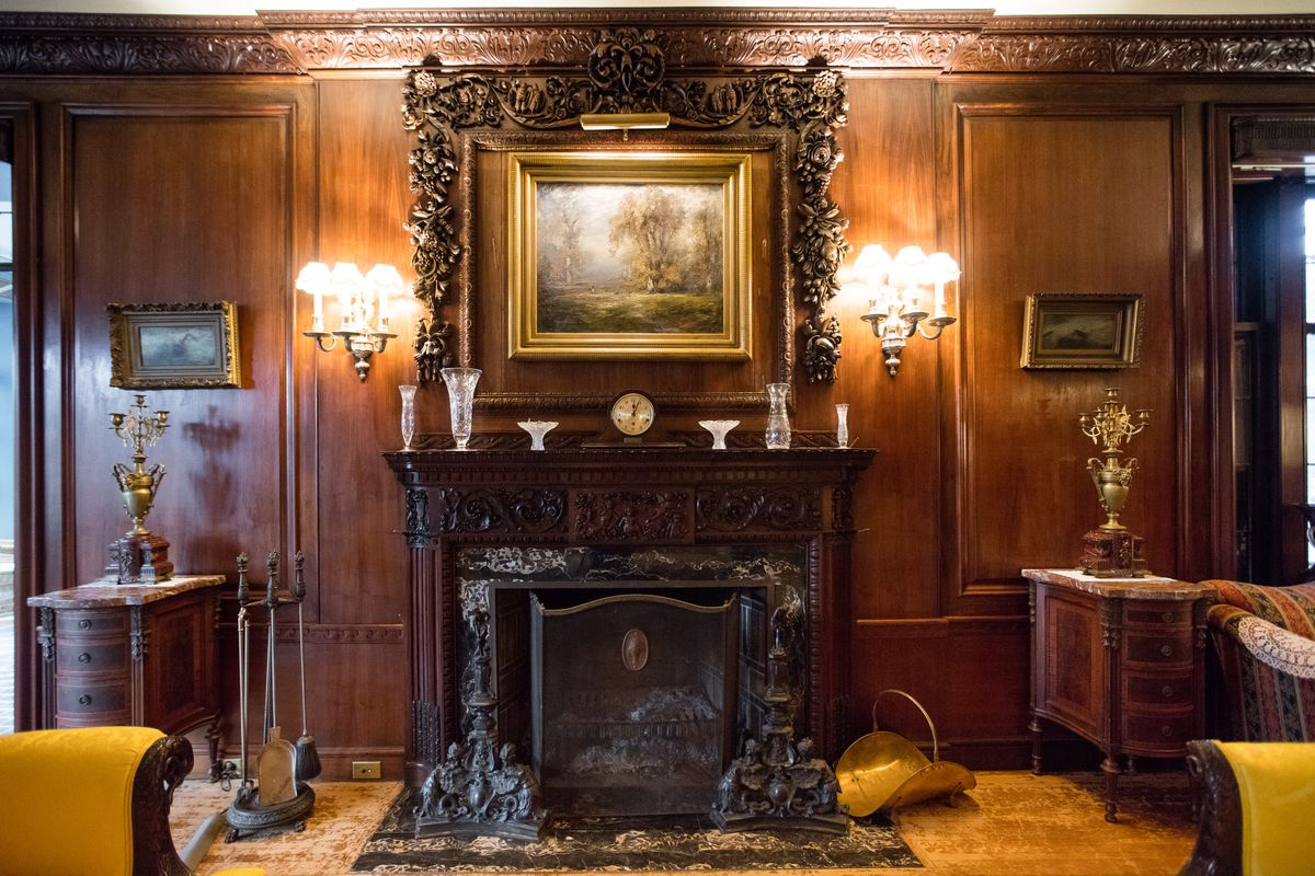 An ornate walnut mantel protrudes from the hand carved  wood paneling that adorns the walls