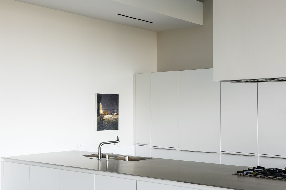 The kitchen has smooth, white cabinets and stainless steel countertops.