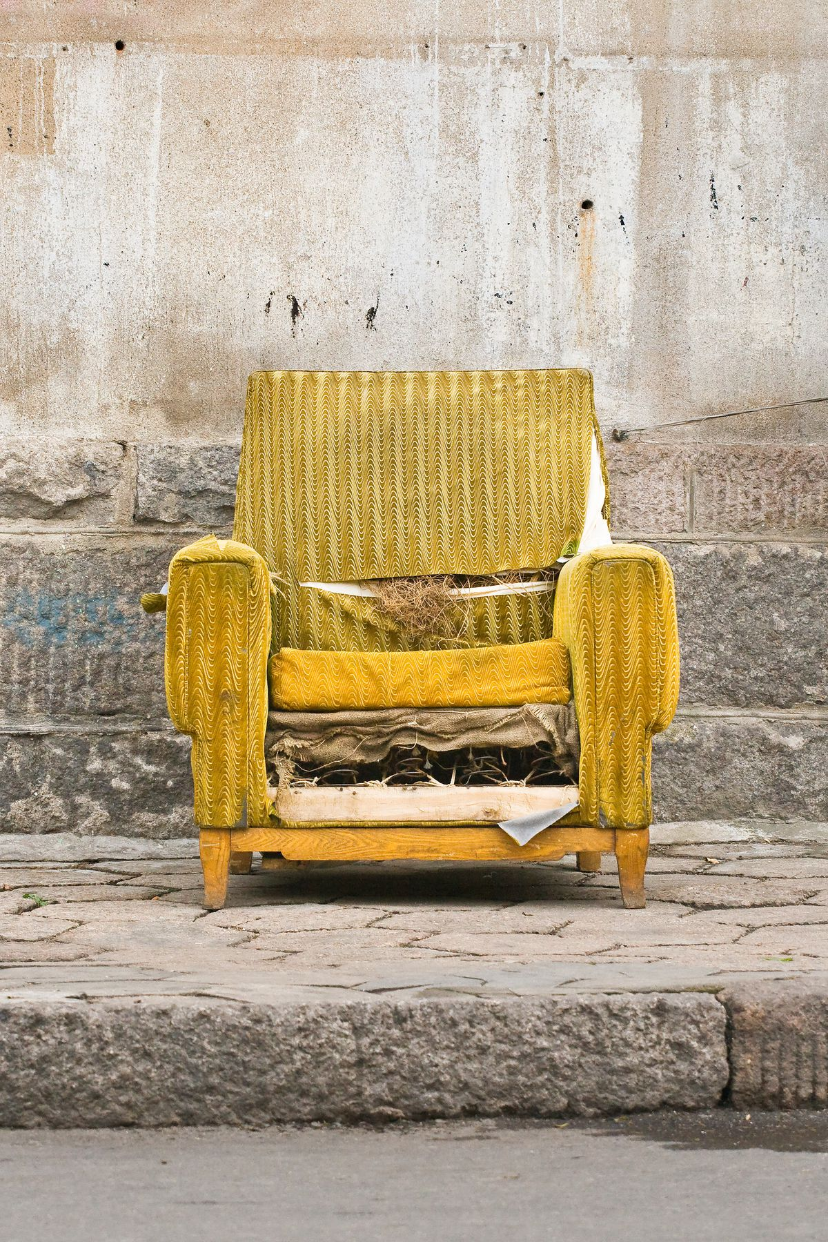 Photo of a ripped, broken, dirty armchair on a concrete sidewalk in front of a concrete wall.