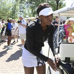 Venus Williams, of the United States, gets out of a golf cart at Stadium Court to play her match against Anastasia Rodionova, of Australia, right, while her sister Serena Williams signs autographs and looks at Venus in the background at left at the Family Circle Cup tennis tournament in Charleston, S.C., Thursday, April 5, 2012. If both sisters win on Friday they would meet in the semifinals on Saturday.