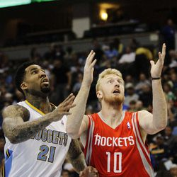 Houston Rockets small forward Chase Budinger (10) grabs a loose ball away from Denver Nuggets small forward Wilson Chandler (21) during the first quarter of an NBA basketball game Sunday, April 15, 2012, in Denver.