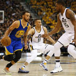 Golden State Warriors guard Stephen Curry #30 attempts to drive past Utah Jazz forward Derrick Favors #15 and guard Dante Exum #11 during game four of the Western Conference Semifinal at Vivant Smart Home Arena in Salt Lake City on Monday, May 8, 2017.