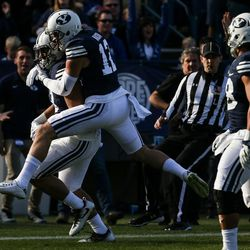 Brigham Young Cougars linebacker Francis Bernard (13) celebrates with defensive back Kai Nacua (12) after Bernard scored a touchdown, putting BYU up 34-9 after the PAT, during a game against the UMass Minutemen at LaVell Edwards Stadium in Provo on Saturday, Nov. 19, 2016.