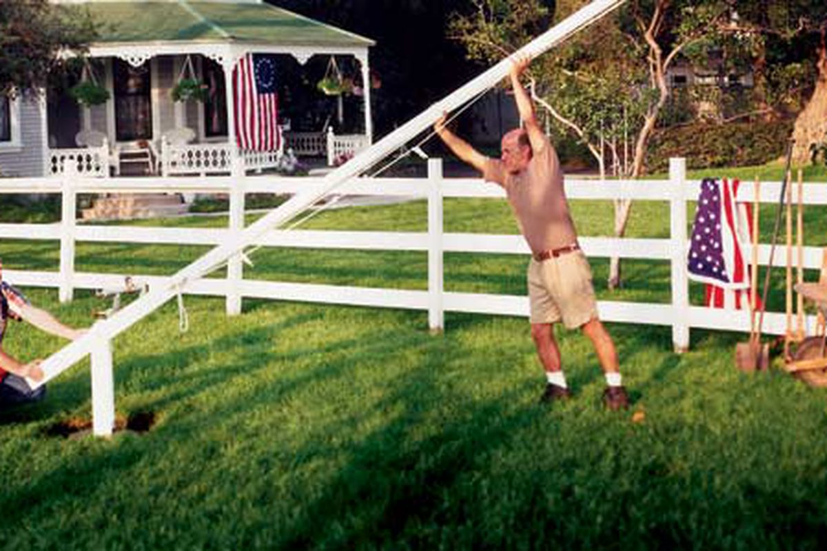 Men Installing An In-Ground Flagpole In Front Of Residence