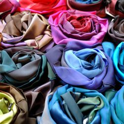 Silk scarves for sale, folded like blooming roses.