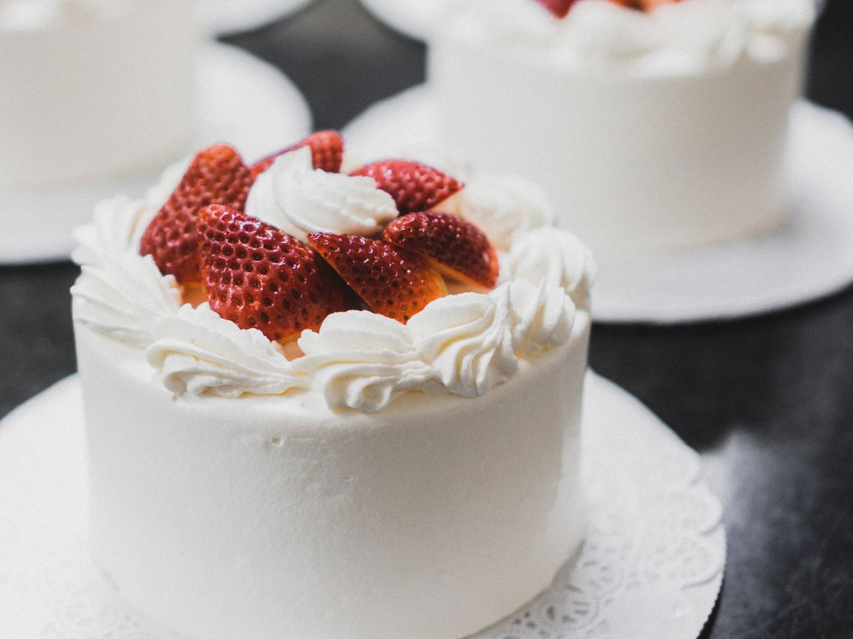 Small cakes on individual cake plates, covered in white frosting, with bright strawberry slices on top