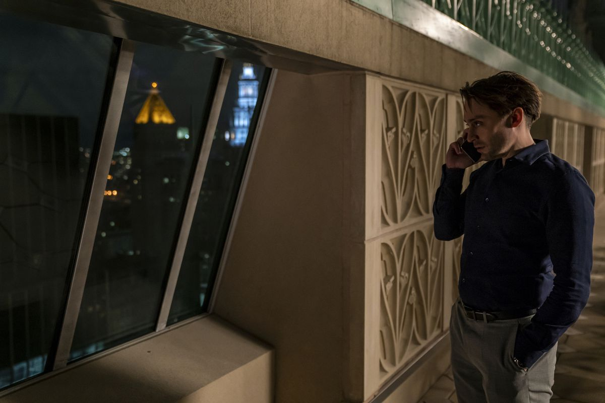 Roman takes a phone call while looking out over the darkened city.