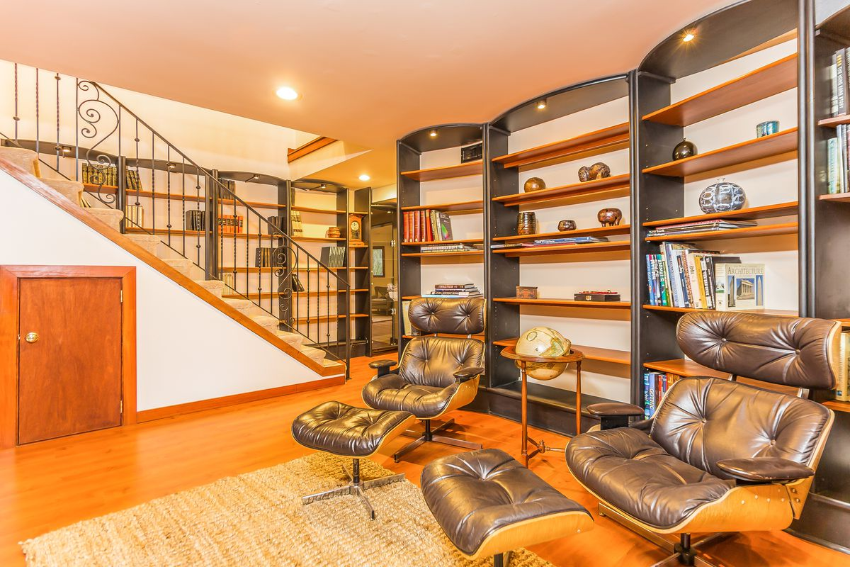A library with a staircase leading upstairs and two leather chairs with footrests