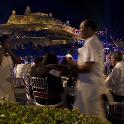 Servers work as guests attend a dinner outside the San Felipe castle during the sixth Summit of the Americas in Cartagena, Colombia, Friday April 13, 2012.  (AP Photo/Carolyn Kaster)