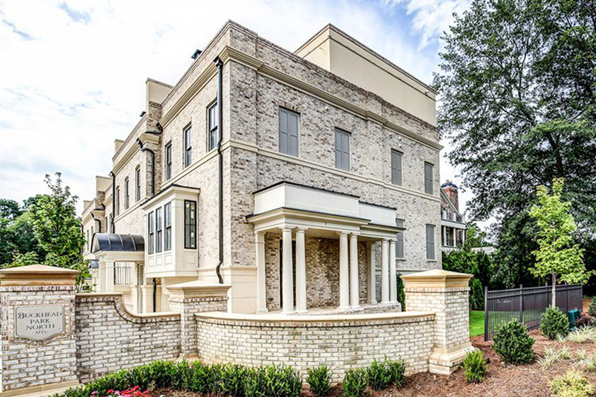 A light brick home with classical details and a rooftop deck.