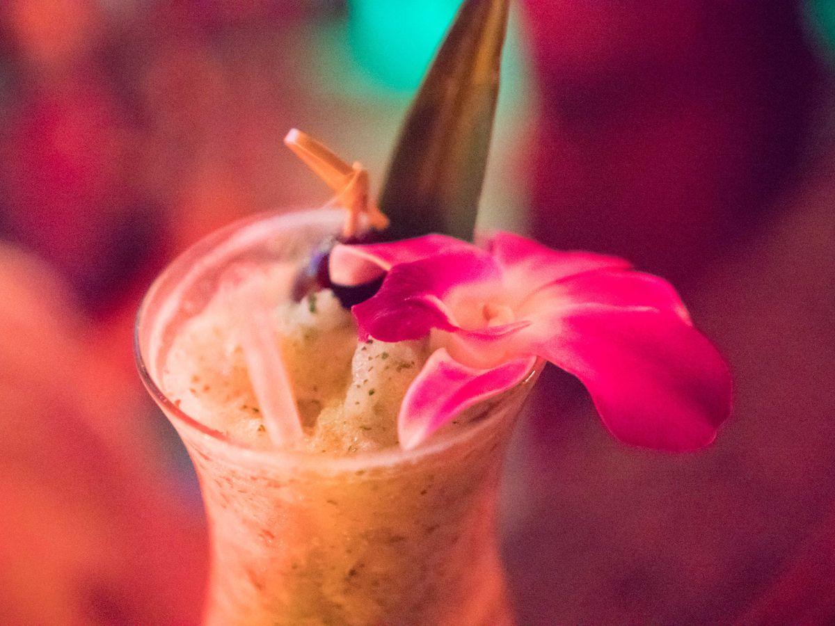 The Kiss My Kukui includes lime, passionfruit, pineapple, and mint, garnished with a flower for tropical flair