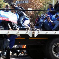 Opposition party Democratic Alliance (DA) supporters take a cover as they are stoned during their protest march against the Congress of South African Trade Unions (Cosatu) for opposing the youth wage subsidy in Johannesburg, South Africa on Tuesday May 15, 2012. The opposition party march in Johannesburg turned violent after union supporters hurled rocks at the leader of South Africa's main opposition party.