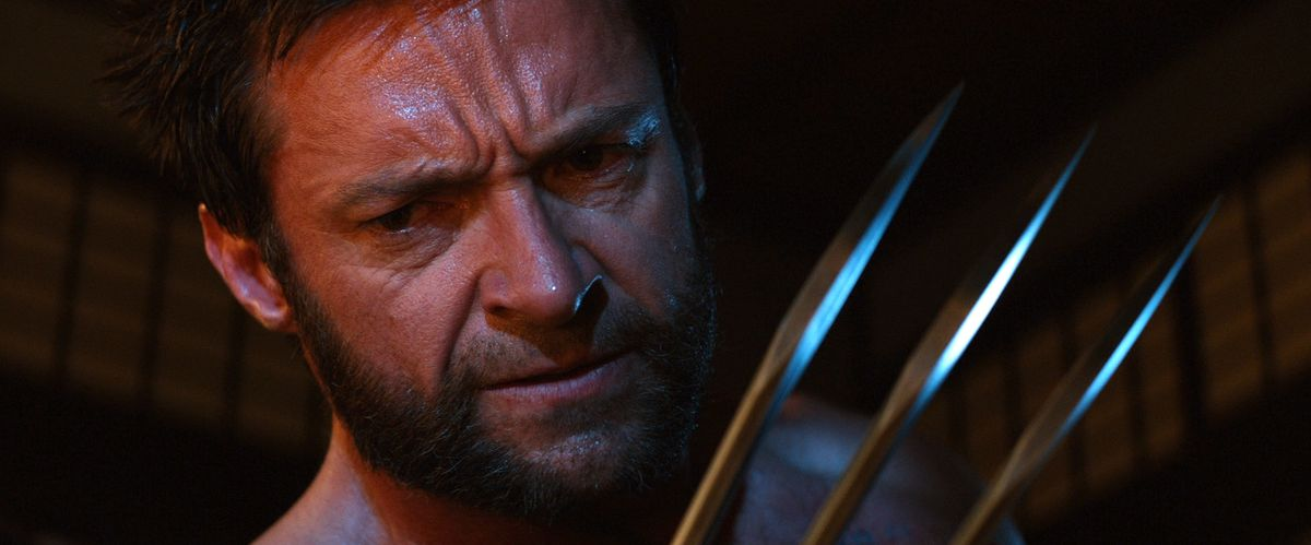 Wolverine stands in close up holding his metal claw up to his face