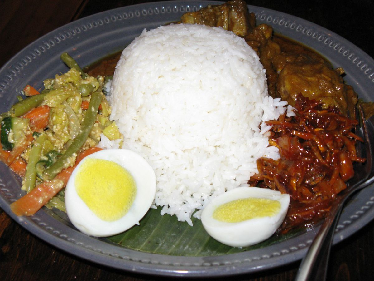A Malaysian fish —curry chicken, rice, and a hard-boiled egg —on a banana leaf on a blue plate