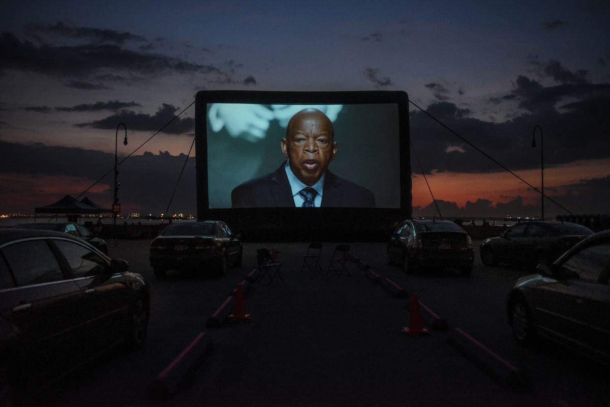 John Lewis appears on an outdoor movie screen, his face framed by dark rows of parked cars, and a sky purple and red from the setting sun.