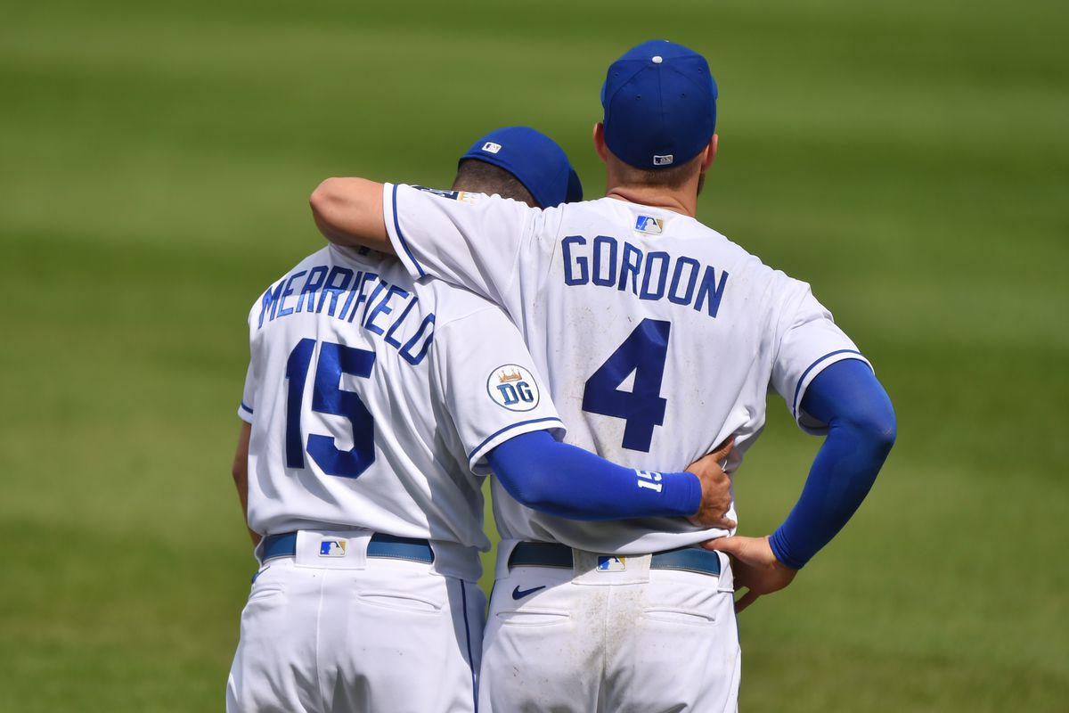 Alex Gordon #4 of the Kansas City Royals receives a hug from teammate Whit Merrifield #15 as the watches a tribute video in his Gordon's honor priori to a game against the Detroit Tigers at Kauffman Stadium on September 26, 2020 in Kansas City, Missouri. Gordon retired from baseball following the ending of the game.