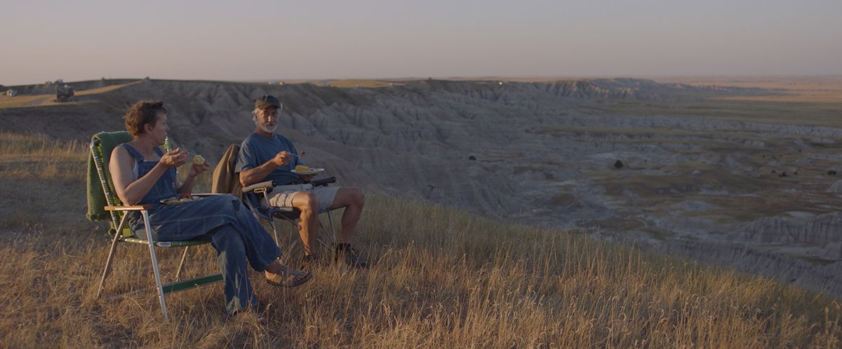 A man and a woman sit in lawn chairs eating dinner overlooking a vast landscape.