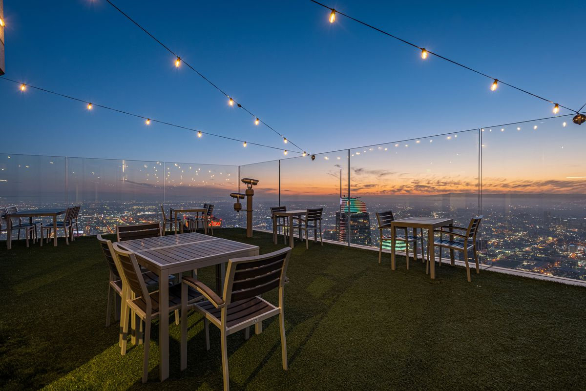 Distanced tables at sunset at a high rooftop patio.